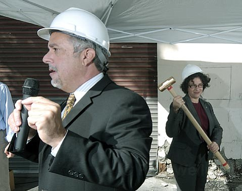 <strong>Razing and raising:</strong>  Mayor Helene Schneider takes a ceremonial swing at the building that used to house Haagen Printing. In its place will go 55 new studio apartments whose rents will range from $408-$800 per month.