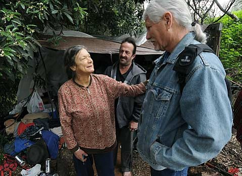 Ken Williams, right, speaks with Cherrie at a homeless camp and gives her a safety card on Friday morning.