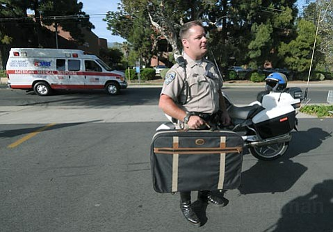 CHP officer James Richards holds the suitcase that caused the scare at the  Castillo Street DMV.