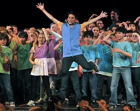 Seventh grader Ulises Perez leaps past fellow cast members in <em>Miguel and His Cell</em>.
