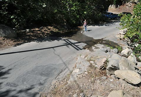 "CRASH SITE REVISITED:""I knew water was there,"" said Erin Tague of her July 14 crash. ""I'd taken this route before, so I exercised a little bit of caution. I have no idea what happened, I completely lost control of the bike. It just flew out from under me. I've never been in so much pain in my entire life. I was paralyzed in the middle of the road."""