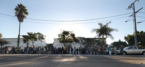 Members of the homeless community line up in front of Casa Esperanza