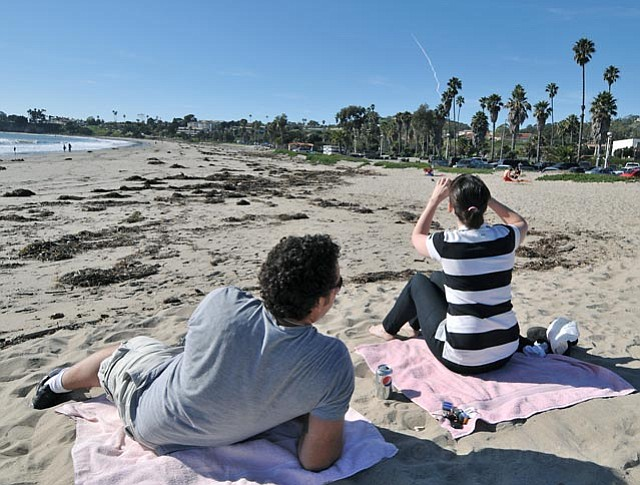 Brandi Roberge (striped shirt) and Marco Dominguez watch, from Leadbetter Beach, the Delta IV rocket that took off from Vandenberg Air Force Base on Jan. 20, 2011
