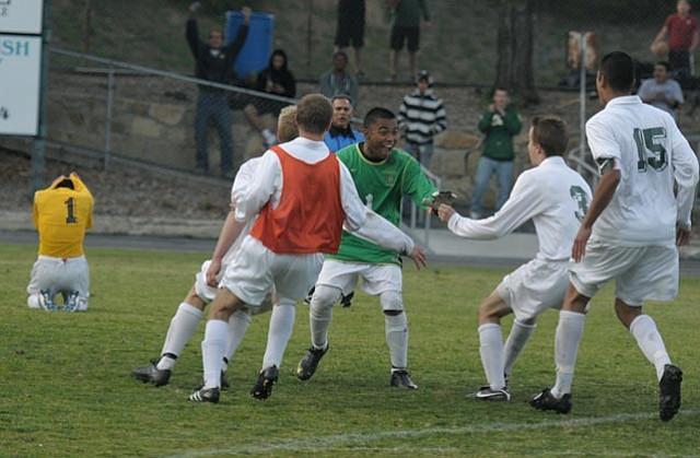 The Dons beginning their celebration around their goalie, Miguel Solis