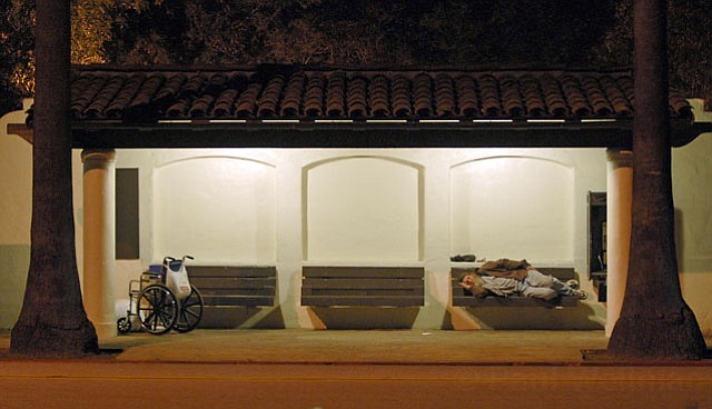 A homeless man sleeps on a bus stop bench on a cold night in February, 2006.