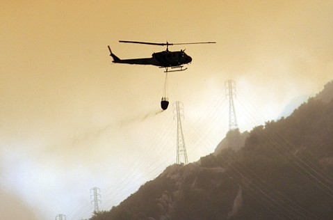 With more than 100 layoffs looming over the Sheriff's Department, questions about the department's four helicopters—one is pictured here deployed during the Gap Fire off Old San Marcos Road—and one plane have grown more pointed.