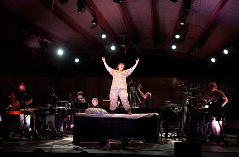 Dawn Upshaw sang George Crumb's <em>The Winds of Destiny</em> from atop an onstage bed in Peter Sellars's dramatic staging. Flanking her are pianist Gilbert Kalish and members of the  red fish blue fish percussion ensemble.
