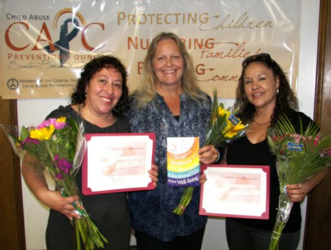 Showing off the booklet created by the parents, Barbara Finch (center), Child Abuse Prevention Council Chair, poses with two of the honored parent leaders (Yoly Monzon, left and Brenda Lopez, right).