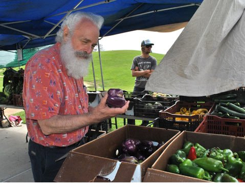 SBCC Anthropology Instructor Paul McDowell inspects a purple bell pepper at the vendor stand.