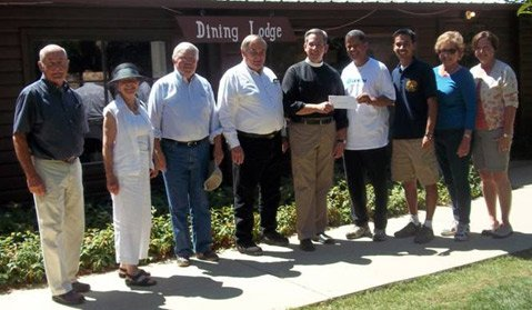 """Pictured at the Circle V Ranch Camp, representatives of St. Mark's-in-the-Valley Episcopal Church presented the Society of St. Vincent de Paul's Circle V Ranch Camp with a $5,000 donation for """"Camperships."""" Left to right: From St. Mark's—Paul Satterblom, Senior Warden; Sharron Luft, Vestry member and Outreach Chair; Richard Nagler, Cellar Classic Committee member; Stephen Pepe, Co-Chair, Cellar Classic; and The Rev. Dr. Randall Day, Priest and Rector. Receiving the check for St. Vincent de Paul—David Fields, Executive Director; Ray Lopez, Camp Director; Sally Corlett, Board Member and Chair, Friends of the Circle V Ranch Camp; and Kathleen Holzheu, Friends of Circle V Ranch Camp member."""