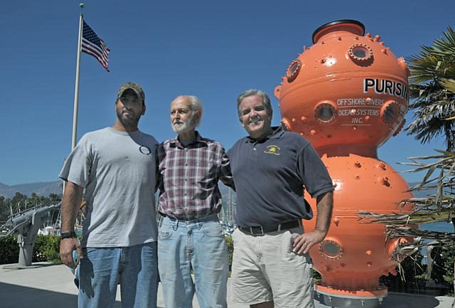from left:  Student Omer Sfar, former Purisima diver Bob Christensen, and SBCC professor Don Barthelmess stand in front of the restored Purisima Diving Bell at the S.B. Maritime Museum.