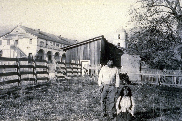 Chumash couple in front of the mission in the 1870s.