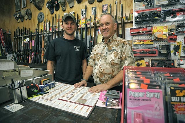 Rick (right) and Kyle Dodge stand in front of their pellet gun selection at Dodge City Shooters Supply