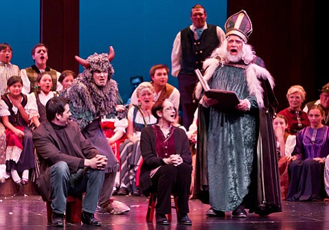Sankt Nikolaus (Simon Williams) reads from his naughty/nice list while surrounded by the cast of Revels.