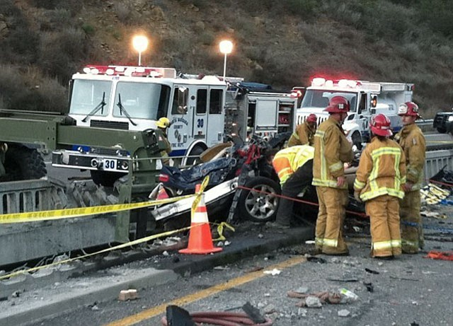 Santa Barbara County fire crews work to secure a car teetering on the side of a bridge on northbound Highway 101 south of Buellton, after it was involved in a crash with a big rig this afternoon. The truck driver was killed and three people were extricated from the vehicle.