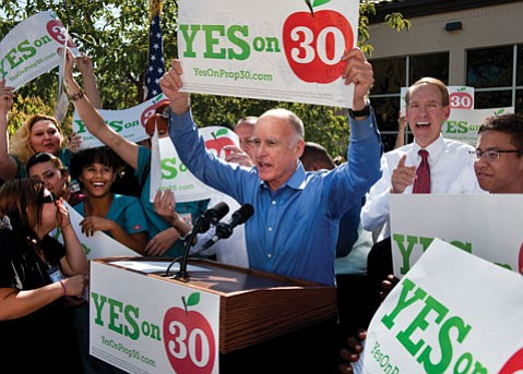 Students, dignitaries, and supporters cheer on Governor Jerry Brown, who holds up a campaign sign and encourages students at Sacramento City College to vote yes for Proposition 30 (October 18, 2012).