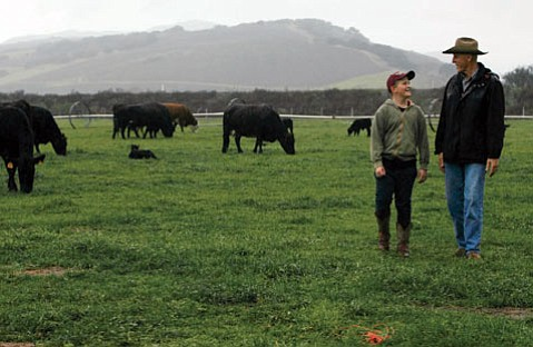 John DeBruin walks with his son, Hudson, 9, through cattle grazing on their property.