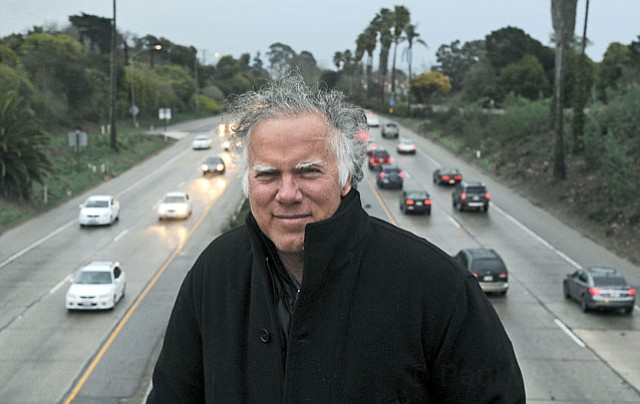 Retired highway builder Ron Pulice stands on the San Ysidro Overpass above Highway 101.