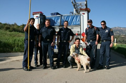 Biscuit poses with her owner and rescuers