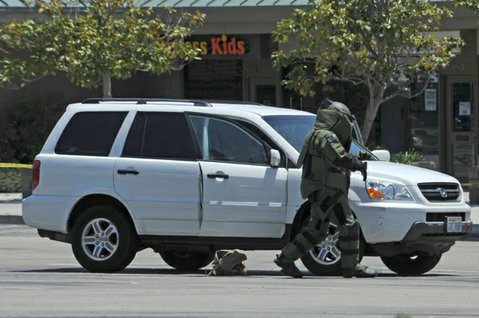 A member of the bomb squad gingerly removes what turned out to be an air soft gun from the suspect vehicle
