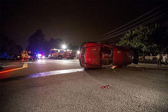 A Ford Escape carrying two SBPD officers rests on its side after it was hit by a drunk driver exiting Highway 101