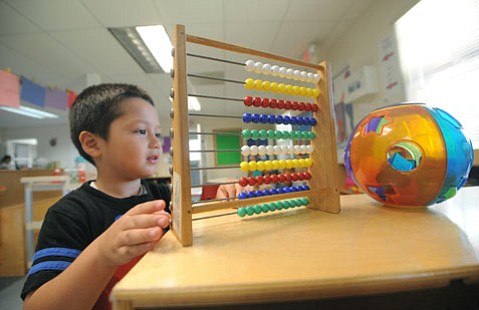 <b>LEARNING SUBTRACTION:</b>  Ethan, 4, a Head Start student at Los Niños on Cota Street, plays at the math station. Two 20-student Head Start classes at Harding elementary school were abolished completely.