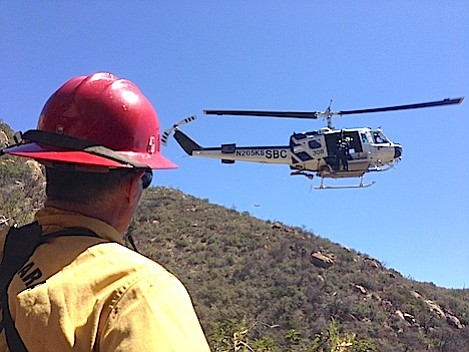 Santa Barbara County firefighter watches as Air Support helicopter prepares to take the dehydrated hiker to safety.