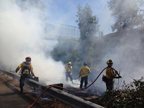 City fire crews douse smoldering brush next to the highway