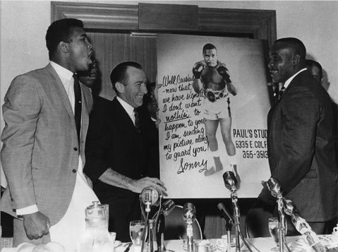 """At the contract signing for the first Ali-Liston fight, Sonny Liston and his manager, Jack Nilon, presented Muhammad Ali with a poster that read: """"Well, Cassius — now that we have signed, I don't want nothin to happen to you — I am sending my picture along to guard you! Sonny."""" Ali, called Cassius Clay back in 1963, responded by punching the poster, to which Liston cautioned him, """"Don't hurt your hand, boy."""""""