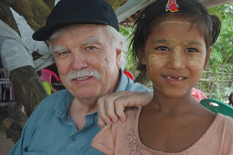 Author Kevin McKiernan poses with a little girl wearing thanaka, a cosmetic paste made from ground bark  popular in Myanmar.