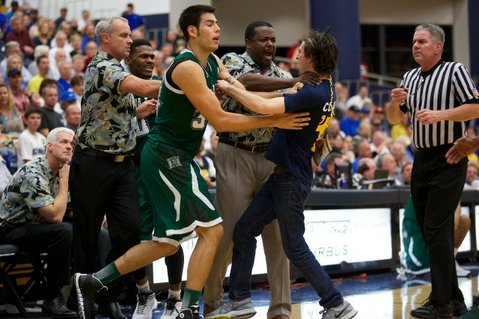An unidentified UCSB basketball fan is shoved away by a Hawaii player and assistant coach after he rushed the court to confront the team's head coach
