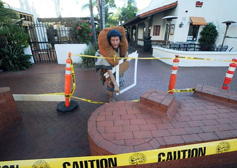 """<b>QUICK FIX:</b> In response to escalating complaints about threatening behavior by """"urban travelers,"""" city officials have transformed the """"Crescent Crossing"""" sculpture, which doubles as a bench, into what appears to be a taped-off crime scene. Jeff, a traveler from New Hampshire, points to a chip in one of the sculpture's bricks."""