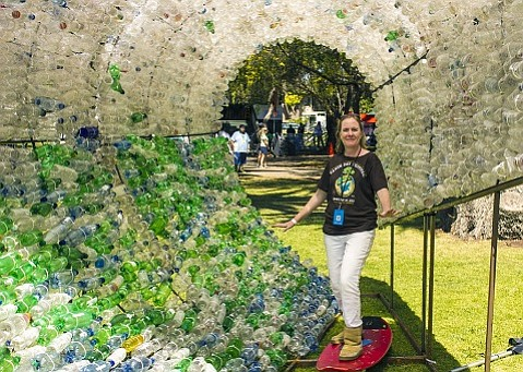 """CEC's Sigrid Wright """"surfing"""" a wave made of single-use plastic bottles at the 2013 Santa Barbara Earth Day Festival."""