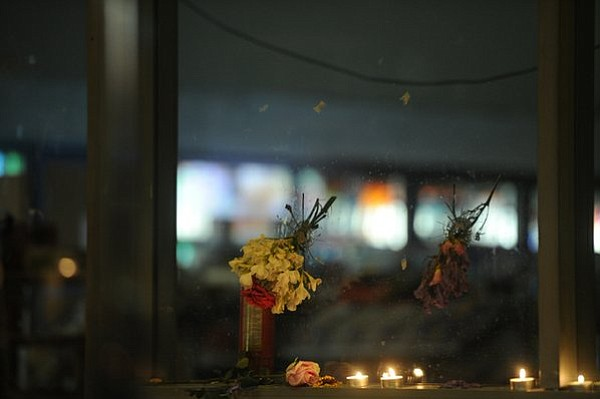 Bullet holes in the windows of IV Deli filled with flowers (May 24, 2014)