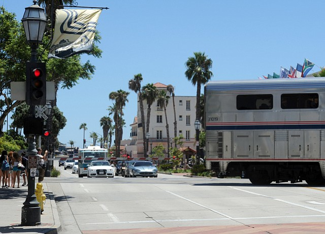Cars and a train run along lower State Street near the planned La Entrada project.