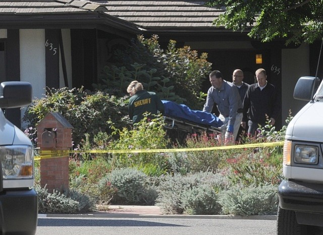 Coroner's Office personnel remove a body from 635 Walnut Park Lane, where four people and a dog were found dead from multiple stab wounds.