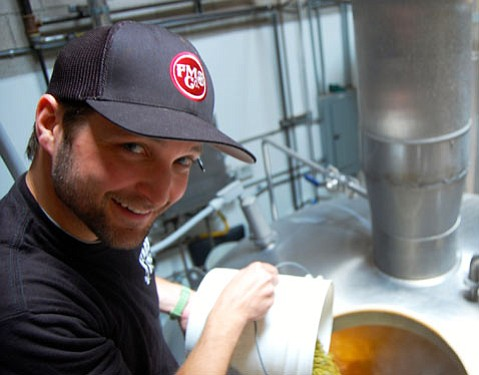 <b>BREW BUD:</b> Brewer Kevin Ashford dumps hops into a bubbling batch of Figueroa Mountain ale.