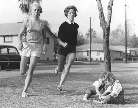 <b>MARATHONERS:</b> Lyn Carman (center) trains with Merry Lepper in 1963. Lepper was the fi rst U.S. woman to fi nish a marathon, and Carman was the third. At the base of the tree are Carman's daughters Maire and Laurie.