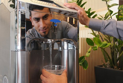 Ernesto Escamilla who works the front desk at Hotel Indigo enjoys a glass of water from the SkyWell machine.
