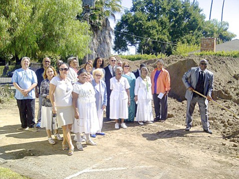 Members of the Second Baptist Church watch Pastor Wallace K. Shepherd put the first shovel in the ground for new senior housing apartments to be built on church grounds.