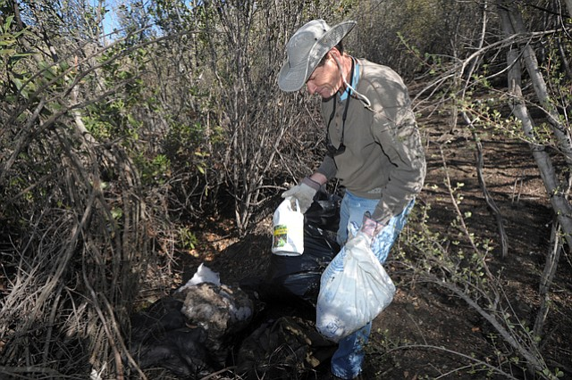 Michael Hess with Los Padres ForestWatch finds and bags a huge cache of old fertilizers