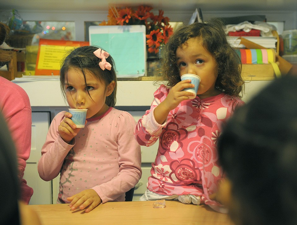 Two girls drink a fruit smoothie at Storyteller Children's Center, which teaches good eating habits to low-income and homeless kids as they're prepped for school