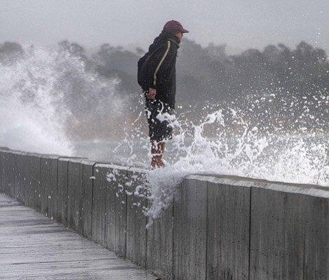 LIQUID LASHING:  A wave crashes against the harbor breakwater during this week's storm.