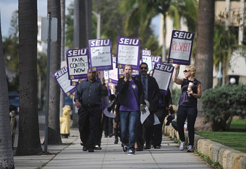 WALK THE LINE:  Union members march down Anacapa Street in front of the downtown courthouse.
