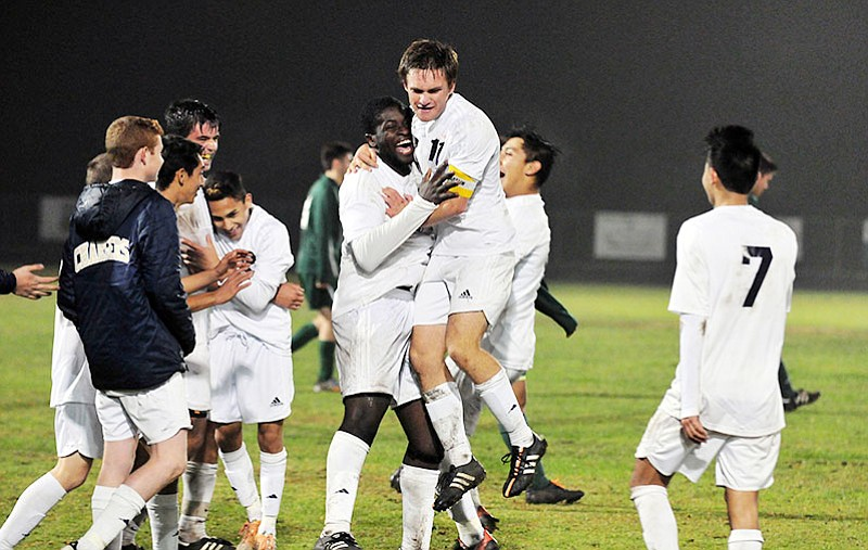Drew Richard leaps into the arms of Manny Nwosu as the Chargers celebrate their victory on Tuesday.