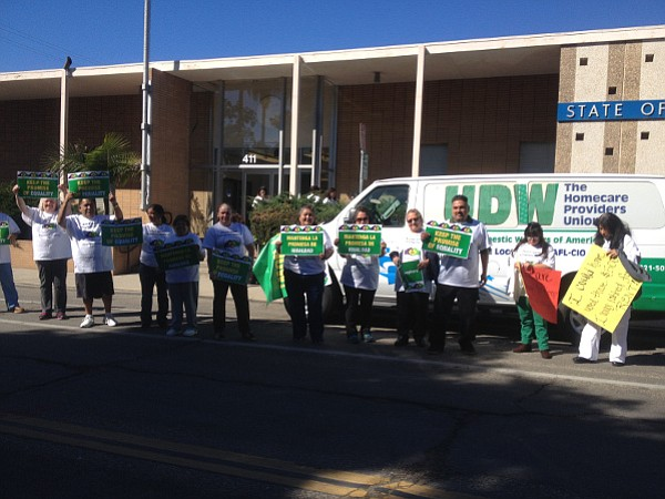 Home-care workers protest in front of the Labor Commission office downtown as cars honk their approval.