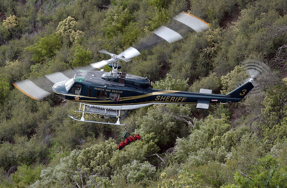 A Sheriff's helicopter carries the remains of a paraglider who fell to his death near Gibraltar Road.  (Mar. 1, 2014)