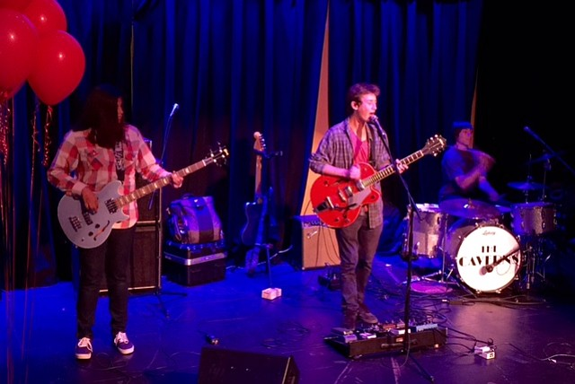 An opening band consisting of high school students performs a Red Hot Chili Peppers cover.