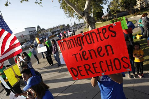 Protesters hold signs Friday on the corner of Main and Broadway in Santa Maria during a May Day rally for workers' and immigrants' rights.