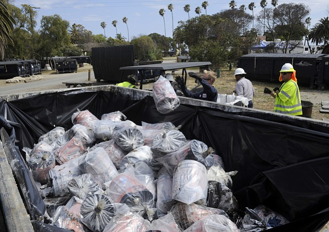 Buckets of oil taken off the beach by concerned citizens are double bagged and put into a waste container at Refugio State Beach (May 21, 2015)